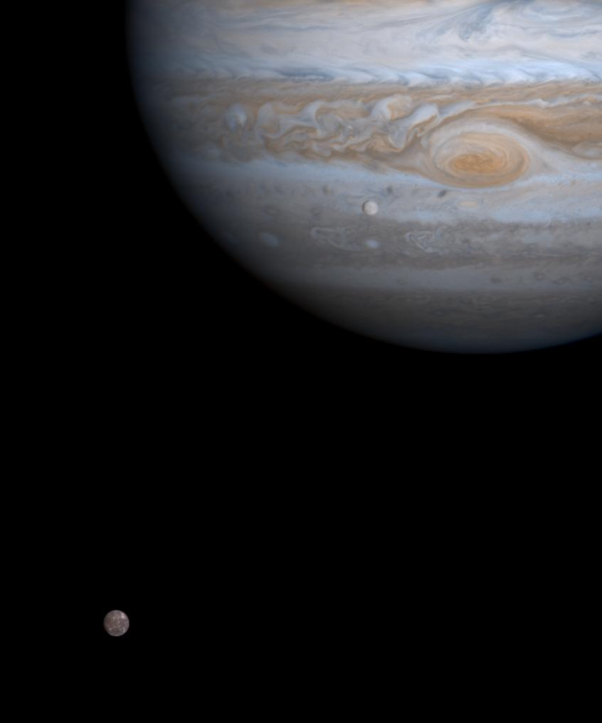 color view of two small moons and jupiter in black space