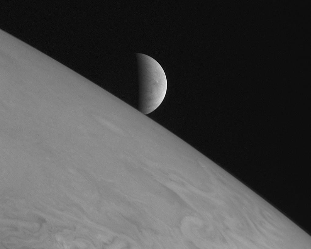 black and white view of half-illuminated moon over curving horizon of large planet
